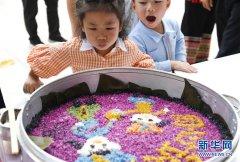 在广西柳州市柳江区进德镇,两名小朋友被五色糯米饭吸